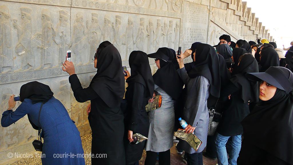Jeunes iraniennes photographiant une frise sculptée sur le site de Persépolis